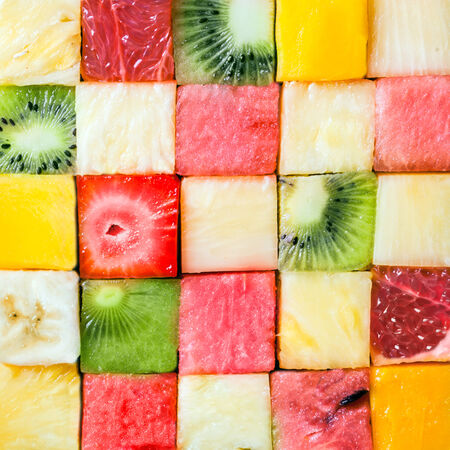 Seamless square background pattern and texture of colorful fresh summer fruit cubes with pineapple, watermelon, banana, kiwifruit, orange, melon and strawberry in a gourmet fruit salad mix Stock Photo