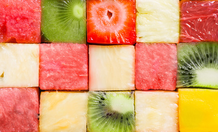 Background texture of diced tropical summer fruit cut in cubes and arranged in rows for a seamless pattern with watermelon, strawberry, kiwifruit, pineapple and melon Фото со стока