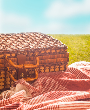 Picnic rug and wicker hamper standing on a green field under a blue sky on a hot summer day for a healthy outdoor lifestyle, closeup in warm sunshine
