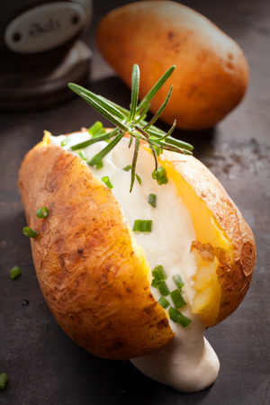 jacket potato: Sliced baked jacket potato cooked over a summer BBQ in foil with sour cream and chopped chives topped with rosemary for a delicious savory appetizer or vegetarian cuisine