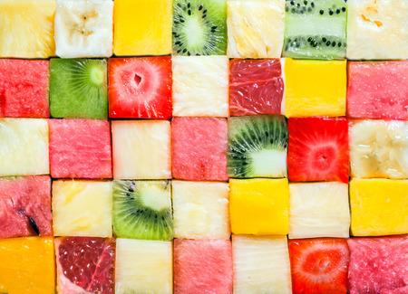 Naadloos patroon als achtergrond en textuur van kleurrijke verse blokjes tropisch fruit blokjes gerangschikt in een geometrisch patroon met meloen, watermeloen, banaan, ananas, aardbeien, kiwi's en grapefruit