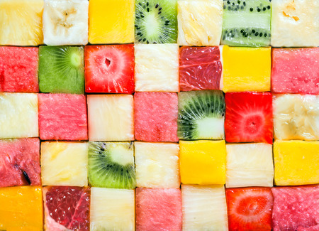 Seamless background pattern and texture of colourful fresh diced tropical fruit cubes arranged in a geometric pattern with melon, watermelon, banana, pineapple, strawberry, kiwifruit and grapefruit Stock Photo