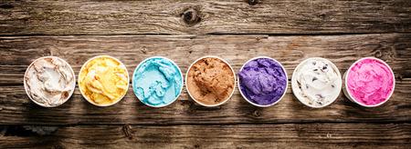 helados: Fila de sabores surtidos y colores de gourmet helado italiano sirvió en tinas de plástico de comida para llevar en una mesa de madera rústica, formato de banner horizontal con copyspace
