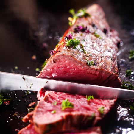 Talla de una porción de delicioso solomillo de carne asada rara de filete sazonado con hierbas frescas con un gran cuchillo de cocina de acero