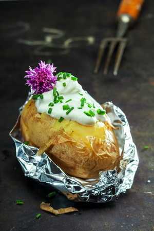 baked potato: Foil baked jacket potato served in the aluminium foil wrapper topped with sour cream and fresh chopped chives and garnished with a purple chive flower