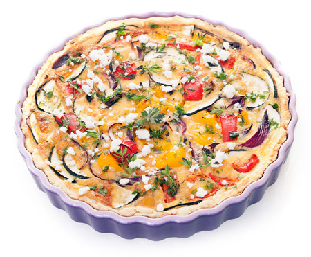 fluted: Vegetarian eggplant quiche in a decorative fluted oven dish with egg, cheese, peppers, tomato and herbs for a healthy meal, high angle isolated on white
