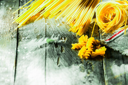 Variety of different Italian dried pasta ingredients arranged in the corner on rustic weather wooden boards with copyspace including spaghetti, fusilli , tagliatelli and linguini photo