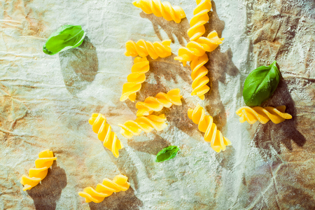 Overhead view of spiral fusilli pasta with fresh basil leaves used as an ingredient in traditional Italian cuisine on crumpled grungy paper Stock Photo - 28081262