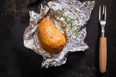 jacket potato: Delicious whole jacket baked potato lying on its crumpled silver aluminium foil wrapper fresh off the summer barbecue, overhead view Stock Photo