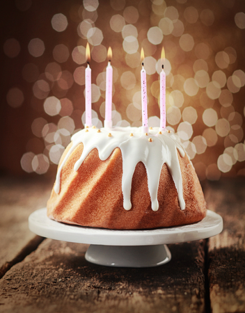 Birthday cake glazed with dripping icing sugar and decorated with pearls topped with four burning candles against a festive party lights bokeh photo