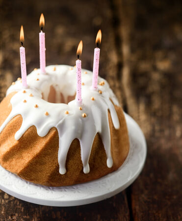 twirled: Party candles burning on a twirled vanilla ring cake decorated with icing and pearls to celebrate a happy birthday , high angle view on a rustic wooden background