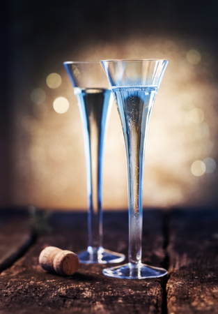 champagne cork: Two elegant blue tinted flutes of luxury champagne with a champagne bottle cork on a rustic wooden bar counter with a backdrop of festive party lights conceptual of a romantic celebration