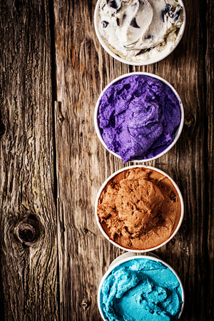 flavor: Gourmet selection of ice cream or frozen yoghurt in a variety of colours and flavours served on a rustic wooden table in a row of plastic takeaway tubs with copyspace Stock Photo