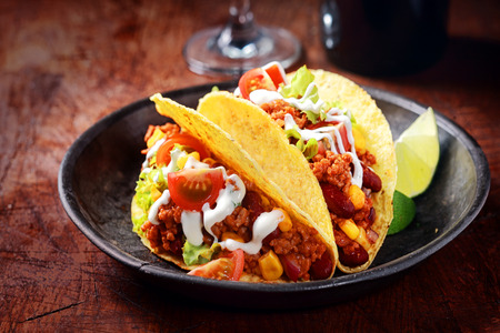 tex: Delicious spicy tacos with meat, salsa and vegetables drizzled with sour cream and served with lemon wedges for a savory snack or lunch