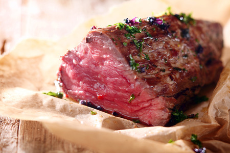 Tender lean rare roast beef seasoned with fresh herbs and spices on a piece of oven paper