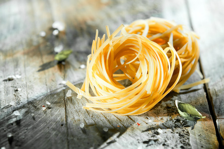 Dried Italian linguine or tagliatelli pasta in coils lying on a rustic grungy grey wooden background with copyspace