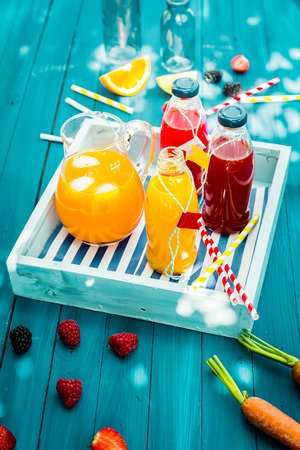 Fresh healthy homemade fruit juice squeezed from citrus, raspberries strawberries and carrots standing on a wooden tray in glass bottle on a turquoise picnic table in dappled summer sunlight