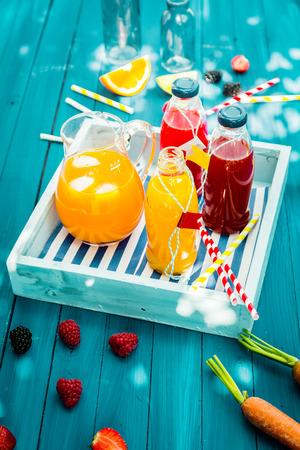 新鲜健康的自制果汁从柑橘,覆盆子,草莓和胡萝卜榨成,放在木托盘上的玻璃瓶放在绿松石野餐桌上,在斑驳的夏日阳光下