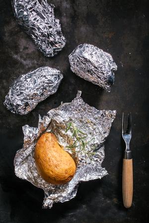 accompagnement: Pommes de terre r�ties dans leur peau dans une feuille d'aluminium sur un barbecue d'�t� �tant d�ball�s pour un accompagnement savoureux pour un repas ou un ap�ritif