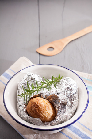 Baked jacket potato in aluminium foil hot off the barbecue lying on the crumpled foil wrapper in a basin with fresh rosemary, high angle view with copyspace photo