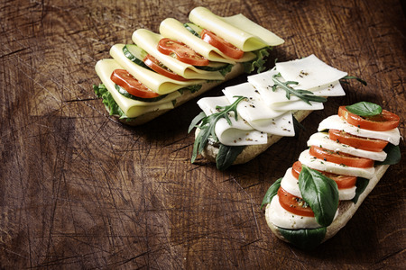 Delicious open vegetarian baguettes topped with assorted cheese including gouda and mozzarella with tomato, lettuce, rocket and basil arranged on a rustic wooden table with copyspace, high angle view photo