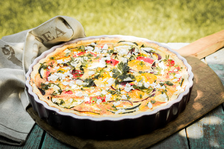Tasty vegetarian quiche on a summer picnic table outdoors with eggplant, eggs, cheese, tomato and herbs for a healthy lunchtime party snack photo