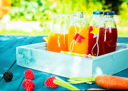 Healthy fresh fruit and vegetable juice blends with citrus, berries and carrots standing ready to drink in glass bottles on a colorful turquoise picnic table in a summer garden photo