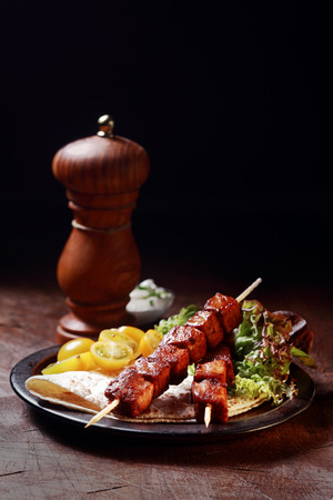 Two delicious spicy grilled pork kebabs served on a plate with fresh salad and tortilla on a rustic wooden table with a pepper mill and copyspace behind photo