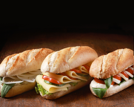 Trio of freshly baked golden vegetarian baguettes with a variety of cheese fillings with herbs and salad ingredients in a row on a wooden counter with dark copyspace behind photo