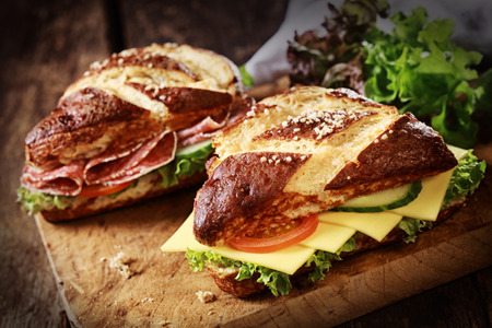 Lye bread rolls , a German and Bavarian speciality bread glazed and baked with lye, with cheese and salami with fresh lettuce, tomato and cucumber on an old wooden board photo