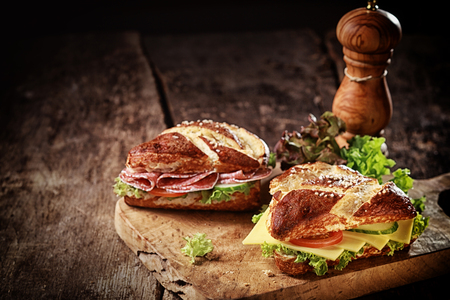 crust crusty: Crusty brown lye bread roll sandwiches with a cheese, salami, lettuce, tomato and cucumber filling on an old grunge board with a wooden pepper mill and copyspace Stock Photo