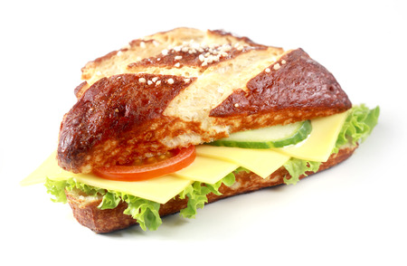 lye: Gouda cheese and salad on a lye bread roll with the traditional crisp brown crust produced by glazing the roll with lye before baking, on white Stock Photo