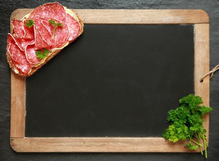 salami: Vista aérea de una vieja escuela de pizarra en blanco de la vendimia con un sándwich de salami y el perejil en esquinas opuestas con copyspace para el menú o la publicidad