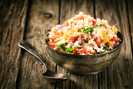 vegan food: Healthy vegetarian quinoa recipe with colourful bell pepper, tomato, onion and fresh herbs in a rustic metal bowl on an old wooden kitchen counter