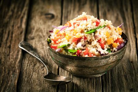 quinua: Saludable receta quinoa vegetariano con colorido pimiento, tomate, cebolla y hierbas frescas en un recipiente de metal r�stico en una vieja mesa de la cocina de madera Foto de archivo