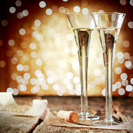 Two elegant flutes of sparkling golden champagne with twirled decorative ribbon against a bokeh of twinkling party lights at a festive celebration photo