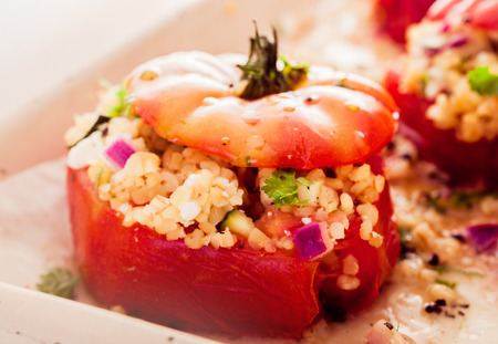 stuffing: Delicious oven baked stuffed tomatoes filled with a couscous grain, onion, and herbs for a healthy appetizer or vegetarian meal Stock Photo