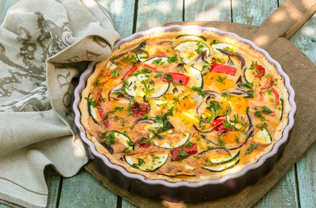 Delicious eggplant savory tart with tomato and fresh herbs in a fluted pie dish served on a wooden board outdoors for a summer picnic