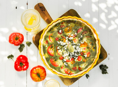 top angle view: Savory quiche with egg, tomatoes, cheese and herbs viewed from above on a wooden chopping board with fresh tomatoes on a rustic white wooden table outdoors