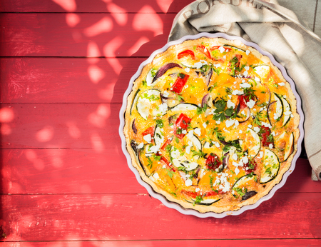 top angle: Savory egg quiche with brinjals or eggplant, tomatoes and cheese for a summer picnic lunch served on a colorful red wooden outdoor garden table in dappled shade Stock Photo