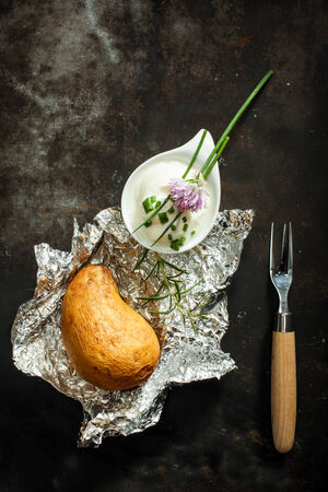 baked potato: Baked jacket potato cooked over a summer barbecue in aluminium foil served with fresh chopped chives and sour cream for a delicious appetizer, overhead view