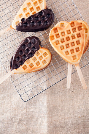 Romantic heart shaped waffle lollipops with a crisp golden wafer dipped on one side in dark chocolate cooling on a wire tray in a kitchen for Valentines or an anniversary