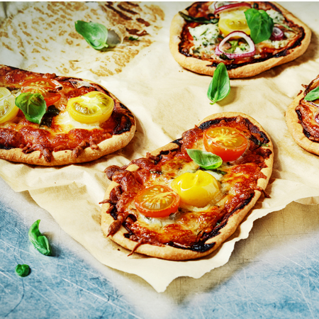 mini oven: Homemade mini pizza with tomato and cheese, fresh basil and onion for a tasty lunchtime snack on grungy stained crumpled paper Stock Photo