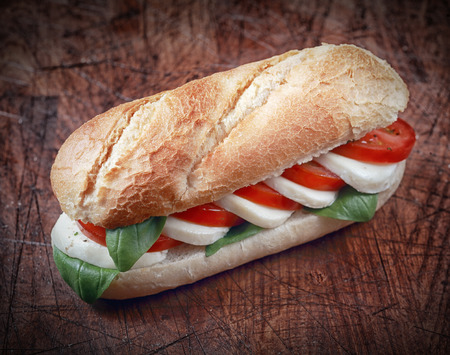 alternating: Alternating slices of mozzarella cheese with ripe red tomato and fresh basil on a crusty golden baguette for a delicious vegetarian snack