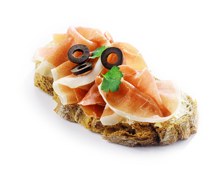 thinly: Gournet thinly sliced spicy cured German schinken ham on bread with sliced black olives and herbs for a delicious traditional snack