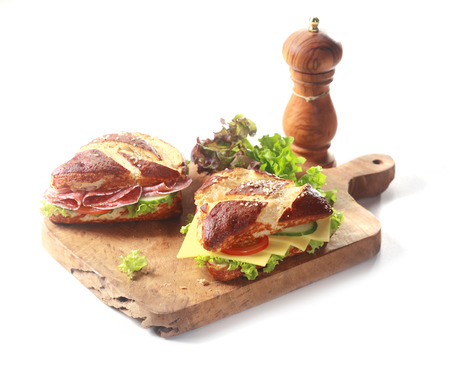 Traditional crusty brown German lye bread rolls, glazed with a lye solution before baking to produce the Maillard reaction, with savory cheese, salami and salad filling on a wooden board on white photo