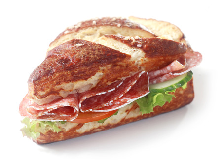 lye: Delicious crusty brown lye bread roll sandwich, a traditional German and Bavarian bread glazed with lye, with spicy salami sausage, lettuce, cucumber and tomato on white
