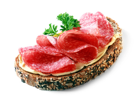 Tasty appetizer of thinly sliced spicy salami on wholewheat bread with a seed crust and liberal spread of butter or margarine topped with parsley, on white photo