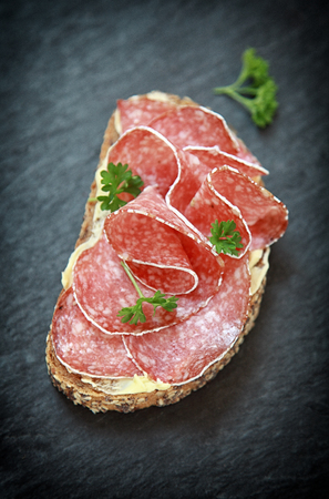 Delicious spicy salami appetizer on buttered bread garnished with fresh green parsley, closeup view from above on an old slate background photo