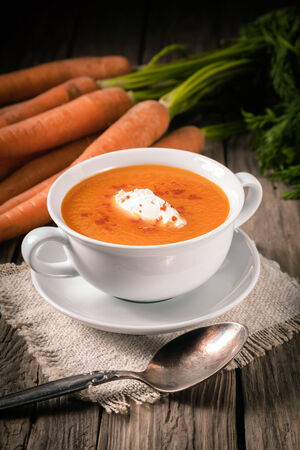 Bowl of homemade tasty carrot soup drizzled with fresh cream and served on a rustic wooden table on hessian photo